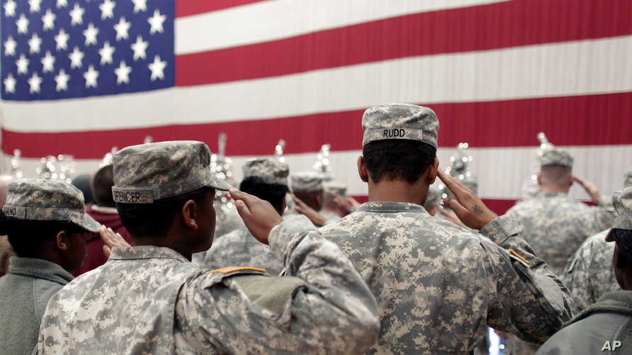 Soldiers salute the U.S. flag during a welcome home ceremony for soldiers at Fort Carson, Colo., Dec. 5, 2012. A Fort Carson soldier has been charged with killing his wife.