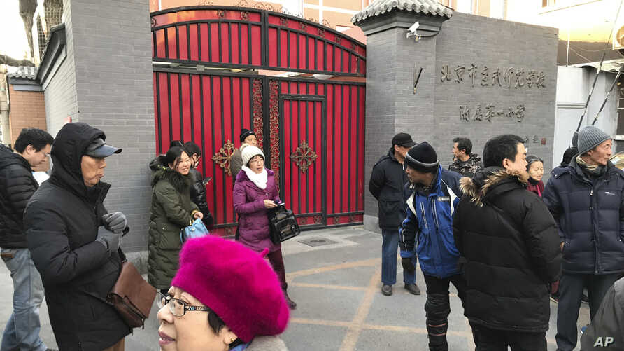 Parents gather at an entrance gate to the Beijing No. 1 Affiliated Elementary School of Xuanwu Normal School following an attack in Beijing, China, Jan. 8, 2019.