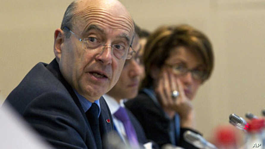 French Foreign Minister Alain Juppe (L) and Syrian Auditing Consultant Maria Chatti attend an international conference of a working group monitoring sanctions against the Syrian regime in Paris, April 17, 2012