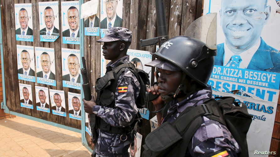 FILE - Policemen stand in front of the gate of opposition leader Kizza Besigye's office in Kampala, Uganda.