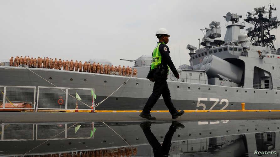 A guard passes by the Russian naval vessel Admiral Vinogradov during a port visit in Manila, Philippines, Oct. 20, 2017.