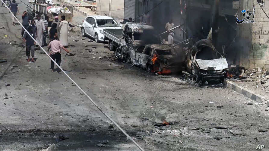 FILE -- Syrian citizens gather near burned cars after airstrikes hit Manbij, in Aleppo province, Syria, in this undated image posted online on July 28, 2016, by supporters of the Islamic State militant group on an anonymous photo sharing website.