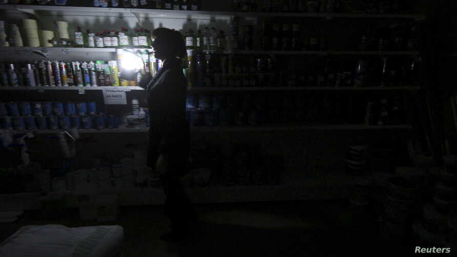An employee works at an appliance shop lit with candles Nov. 22, 2015, due to a power cut in Simferopol, Crimea.