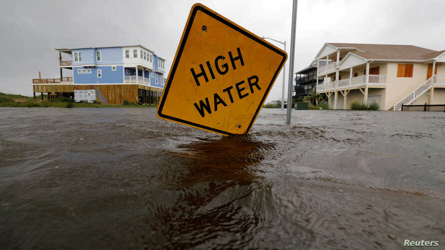 Floodwaters lap at a high water warning sign that was partially pushed over by Hurricane Florence on Oak Island, N.C., Sept. 15, 2018.