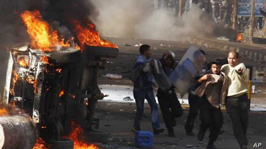 Police and unidentified people are seen in the streets during a demonstration in Suez, Egypt, Jan 28, 2011
