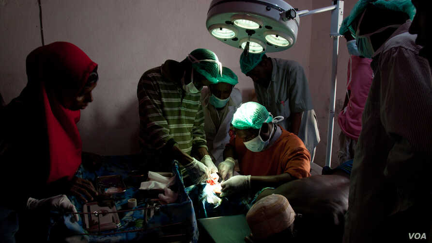 Surgeons-in-training close an incision in the new operating theater, Ras Kamboni, Somalia, July 6, 2012. (R. Gogineni / VOA)
