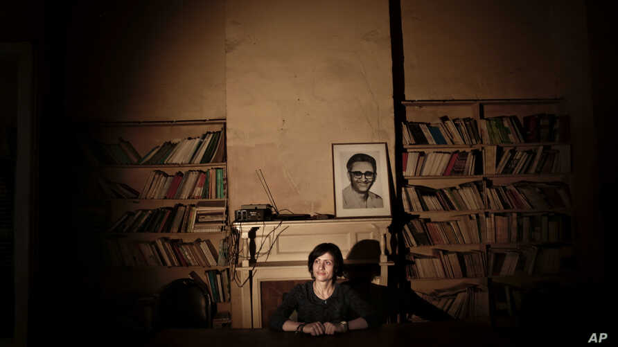 FILE - Basma Abdel-Aziz poses at an old bookshop in downtown Cairo, Egypt, Sept. 27, 2016. The effects of autocracy on people and society has long been the focus of research for Abdel-Aziz, an author and activist who is one of Egypt's keenest observe