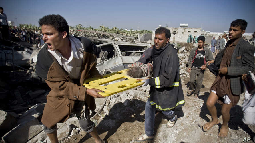 People carry the body of a child they uncovered from under the rubble of houses destroyed by Saudi airstrikes near Sanaa Airport, Yemen, March 26, 2015.