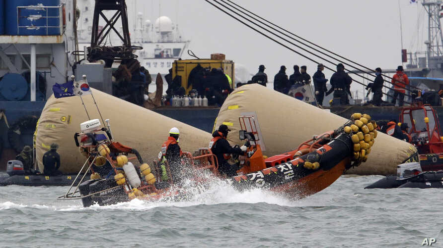 Searchers and divers look for people believed to have been trapped in the sunken ferry boat Sewol near the buoys which were installed to mark the vessel in the water off the southern coast near Jindo, south of Seoul, South Korea, April 22, 2014.