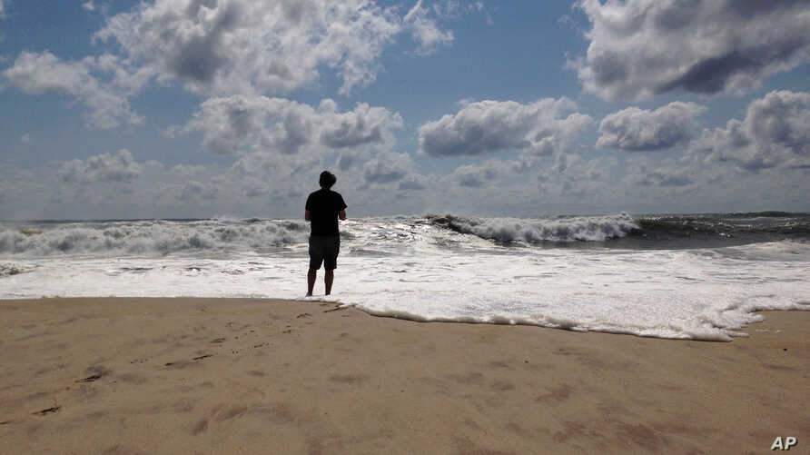 A beachgoer stands at the edge of the water, Sunday, Sept. 4, 2016, in Bridgehampton, N.Y., on the southeastern shore of Long Island, where the effects of storm system Hermine could be seen in the rough surf and a ban on swimming.