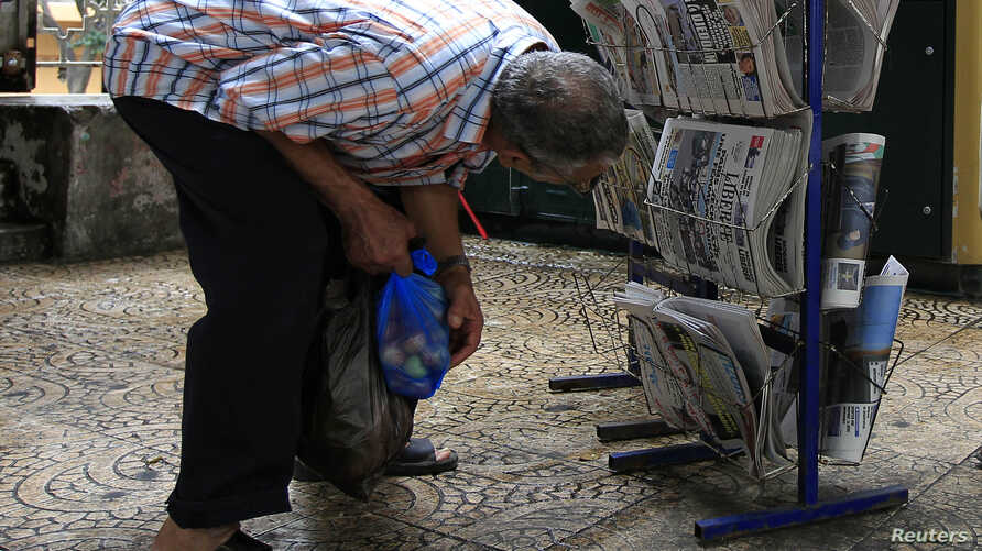 FILE - A man looks at newspapers on display in Algiers, Sept. 21, 2010.