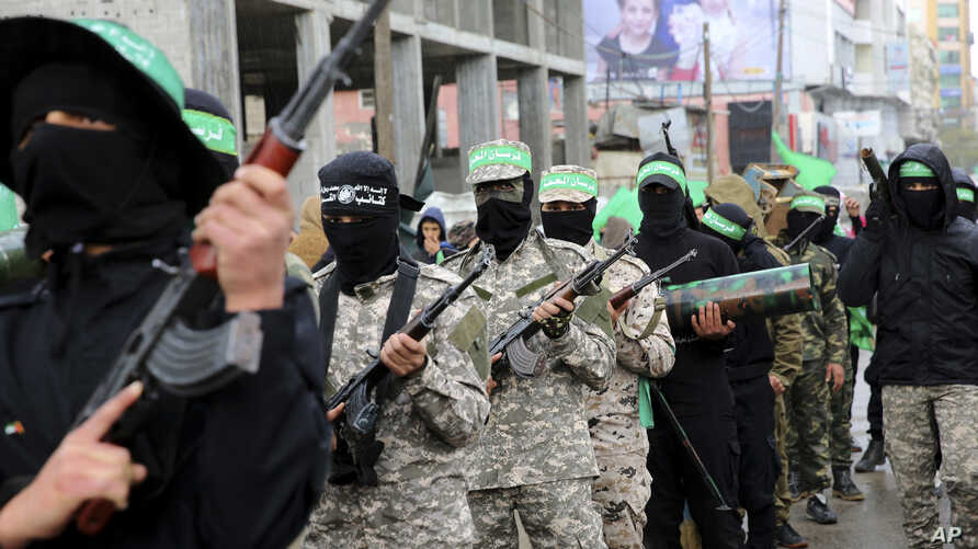FILE - Masked militants from a military wing of Hamas commemorate the 29th anniversary of their group, in Gaza City, Dec. 14, 2016.