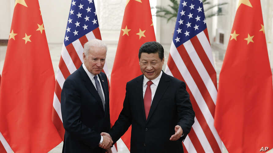 Chinese President Xi Jinping, right, shakes hands with  U.S Vice President Joe Biden, left, as they pose for photos at the Great Hall of the People in Beijing, Dec. 4, 2013.