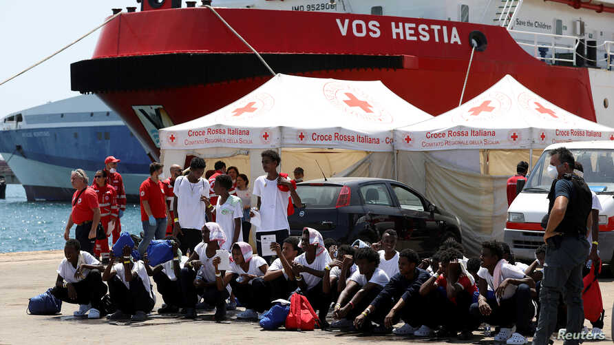 """FILE - Migrants sit on the ground after disembarking from Vos Hestia ship of NGO """"Save the Children"""" in the Sicilian harbor of Augusta, Italy, Aug. 4, 2017."""