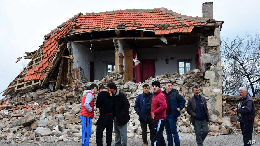 Villagers stand in front of a damaged house after two quakes, both with preliminary magnitudes of 5.3, jolted Turkey's northern Aegean coast, in Yukarikoy village Canakkale province, Monday, Feb. 6, 2017, damaging dozens of homes in at least five vil