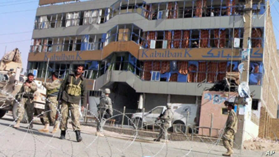 US soldiers and Afghan security forces stand guard at the site of a car bomb in front of a branch of the Kabul bank in Kandahar on 27 Dec 2010