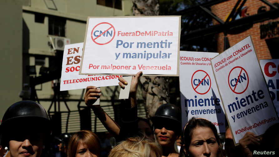 Supporters of Venezuela's President Nicolas Maduro hold placards during a gathering to support Maduro's government order of suspension of CNN's Spanish-language service outside the National Commission of Telecommunications (CONATEL), in Caracas, Vene