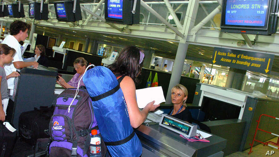 FILE - Passengers en route to London check in at Biarritz airport, southwestern France, Aug. 11, 2006. The U.S. is expected to broaden its ban on in-flight laptops and tablets to include planes from the European Union.