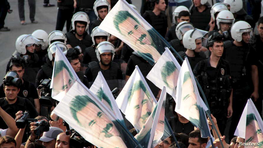 Demonstrators hold flags with pictures of imprisoned Kurdish rebel leader Abdullah Ocalan, during a protest against latest security operations in Diyarbakir, Turkey, September 6, 2015.