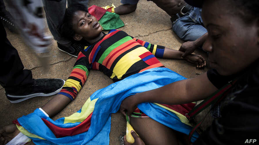 A Congolese protester lies on the ground after police opened fire wth rubber bullets whilst they protest outside the Democratic Republic of the Congo's Embassy in defiance of their President, Joseph Kabila, Dec. 20, 2016 in Pretoria, South Africa.
