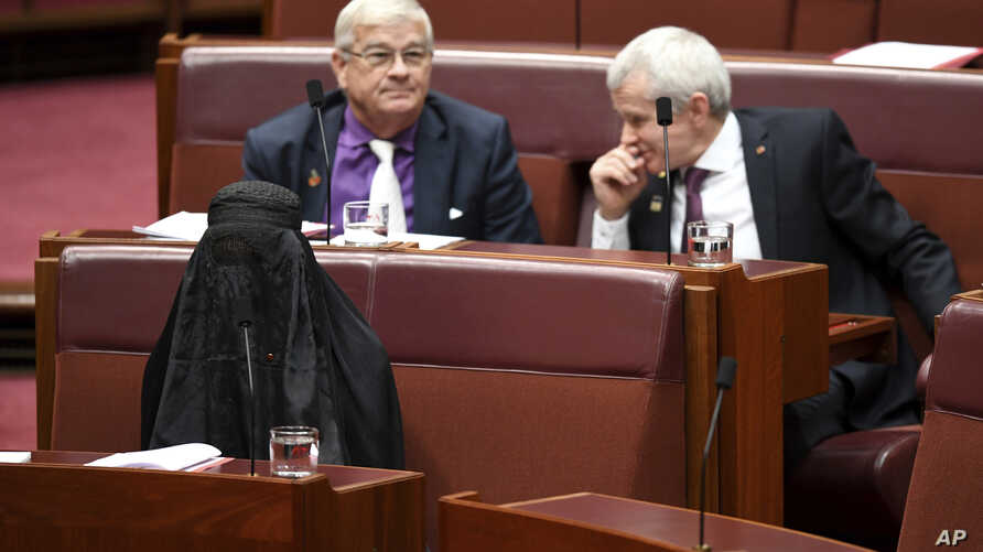 Sen. Pauline Hanson, bottom left, wears a burqa during question time in the Senate chamber at Parliament House in Canberra, Australia, Aug. 17, 2017.