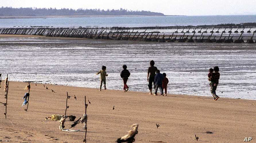 FILE - A family strolls the beaches with shores are lined with iron staves and the land's edge lined with mines, on Taiwan's Kinmen Island, 1.2 miles off China's south east coast, Dec. 13, 2001.