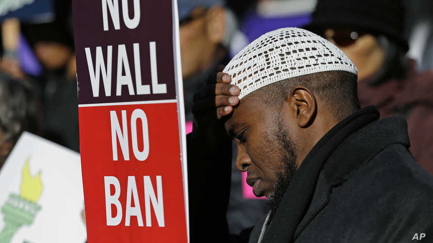 """FILE - Abdirahman """"OJ"""" Mohamed, of Seattle, holds a sign that reads """"No Wall No Ban,"""" during a protest against federal efforts to restrict immigration, Dec. 6, 2017, outside a federal courthouse in Seattle."""