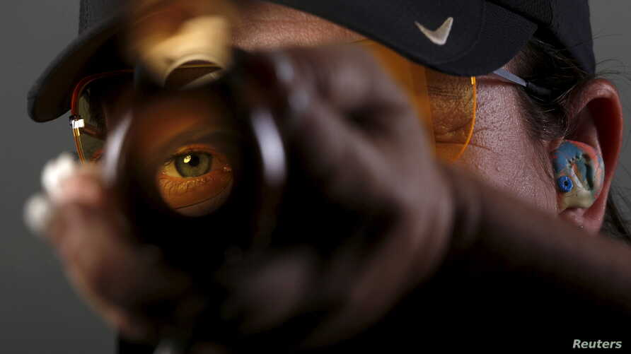 Shooting competitor Kim Rhode looks down the barrel of her shotgun as she poses for a portrait at the U.S. Olympic Committee Media Summit in Beverly Hills, Los Angeles, California, March 8, 2016.