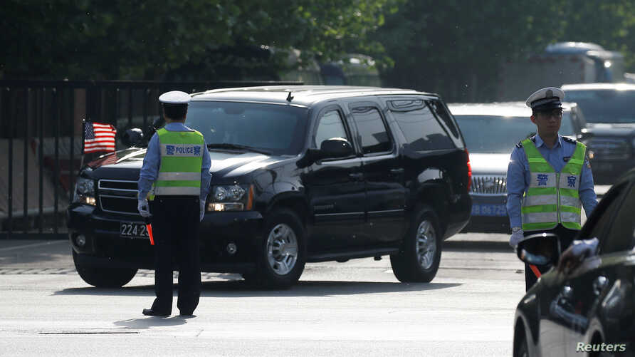 FILE - A motorcade leaves the U.S. Embassy after U.S. officials had trade talks with Chinese counterparts, in Beijing, China, May 4, 2018.