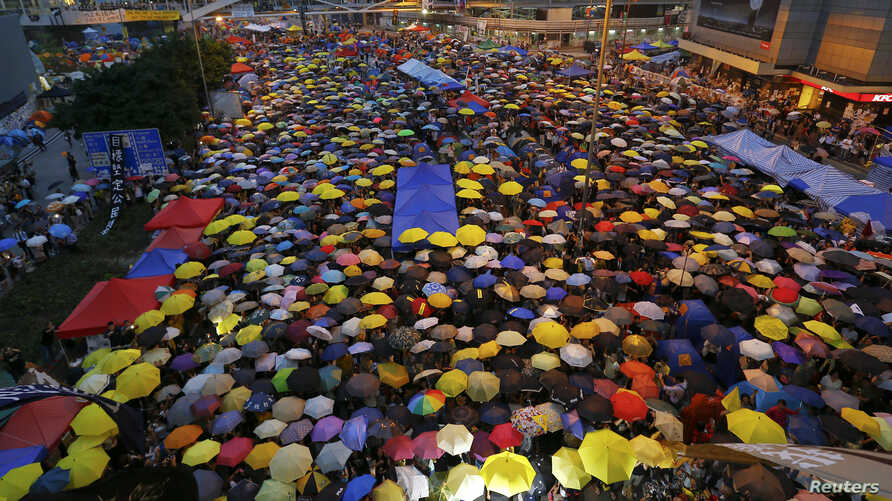 Protesters open their umbrellas, symbols of pro-democracy movement, as they mark exactly one month since they took the streets in Hong Kong's financial central district October 28, 2014. Hong Kong has been roiled by a tenacious, month-long student-le...