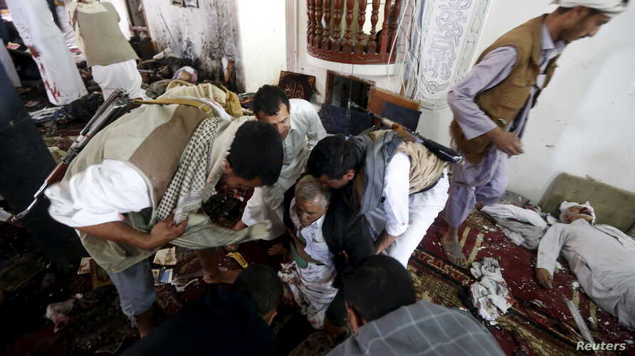 People help an injured man at the scene of a suicide bombing inside a mosque in Sana'a, Yemen, March 20, 2015.