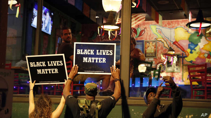 FILE - Protesters hold up signs as restaurant patrons look out the window in St. Louis, Missouri, Sept. 15, 2017.