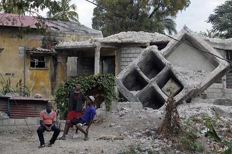 People sit outside a house that was destroyed by the January 2010 earthquake in Port-au-Prince, January 3, 2012.