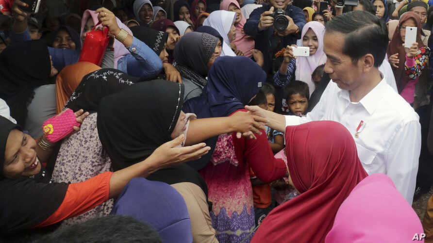 Indonesian President Joko Widodo, right, is greeted by earthquake survivors during his visit at a temporary shelter in Tringgading, Aceh province, Indonesia, Dec. 9, 2016.