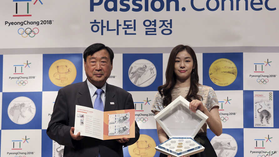 FILE - Former South Korean Olympic figure skating champion Yuna Kim, right, an honorary ambassador for the 2018 Pyeongchang Winter Olympics, and Lee hee-beom, president of the Pyeongchang Organizing Committee for the 2018 Olympic and Paralympic games