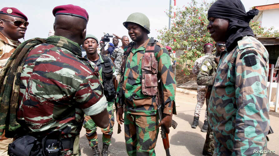 Lieutenant-Colonel Issiaka Ouattara, named Wattao, and Lieutenant-Colonel Cherif Ousmane greet mutinous soldiers, at the airport in Bouake, Ivory Coast, Jan. 13, 2017.