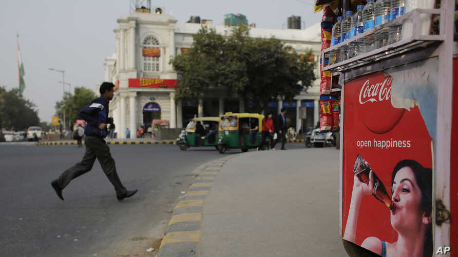 An Indian pedestrian crosses a road near roadside kiosk with a Coca-cola advertisement in New Delhi, India, Feb. 12, 2016. Coca-Cola suspended bottling at three plants in India, including one in the parched northwest where farmers have been protestin