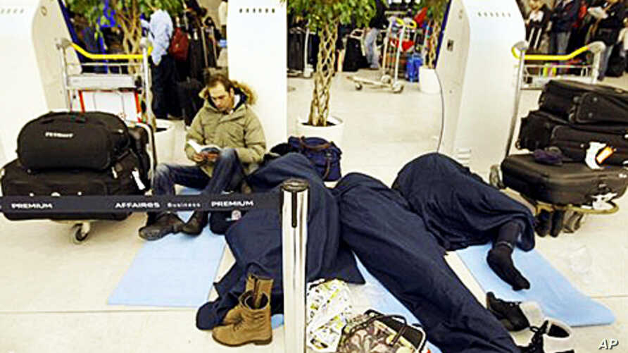 Passengers wait for their flights in a terminal after sleeping a night at the Charles-de-Gaulle Roissy airport, Paris, 24 Dec 2010