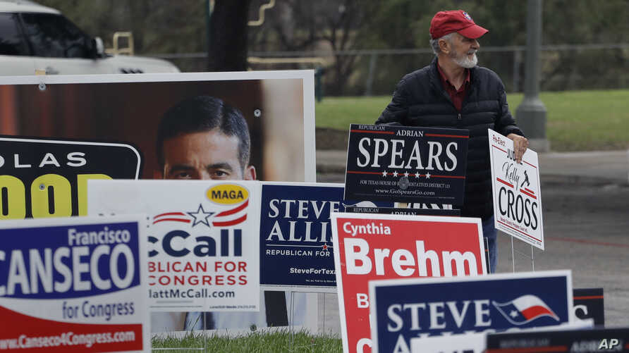 Jim Mathis looks to place a campaign sign near a polling site as early voting begins, Feb. 20, 2018, in San Antonio. Early voting in Texas runs though March 2, 2018.