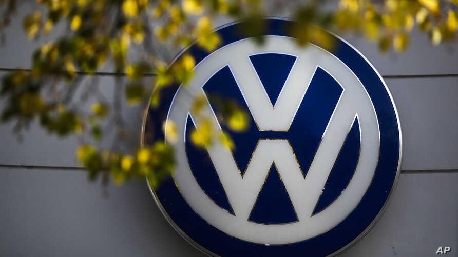 FILE - The VW sign of Germany's car company Volkswagen is displayed at the building of a company's retailer in, Berlin, Germany.