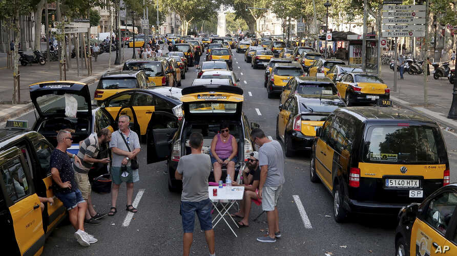 Taxi drivers block the Gran Via avenue in Barcelona, Spain, July 30, 2018. Taxi drivers in Barcelona are blocking traffic on a major thoroughfare as part of an indefinite strike to protest the use of ride-hailing apps like Uber and Cabify.
