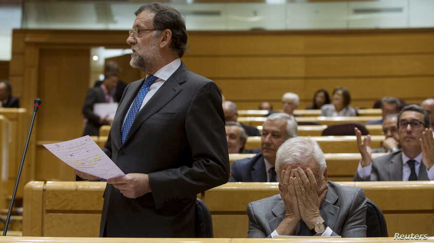 Spain's Prime Minister Mariano Rajoy, left, speaks as Foreign Minister Jose Manuel Garcia-Margallo reacts during the cabinet control session at the Senate in Madrid, Spain, May 26, 2015.