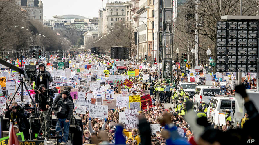 FILE - People hold the March for Our Lives rally in Washington in support of gun control, March 24, 2018. It's far from certain that the young people behind the movement will be a political force at the ballot box this fall.
