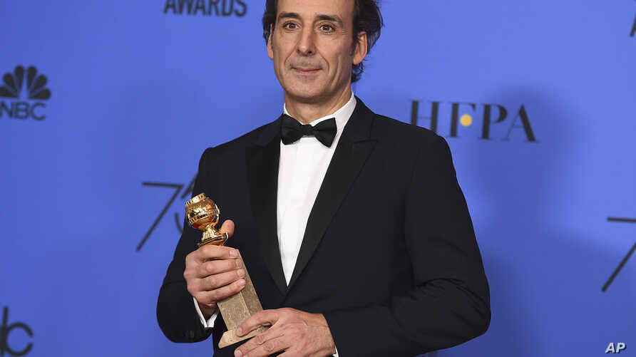 """Alexandre Desplat poses in the press room with the award for best original score - motion picture for """"The Shape of Water"""" at the 75th annual Golden Globe Awards at the Beverly Hilton Hotel, Jan. 7, 2018, in Beverly Hills, Calif."""