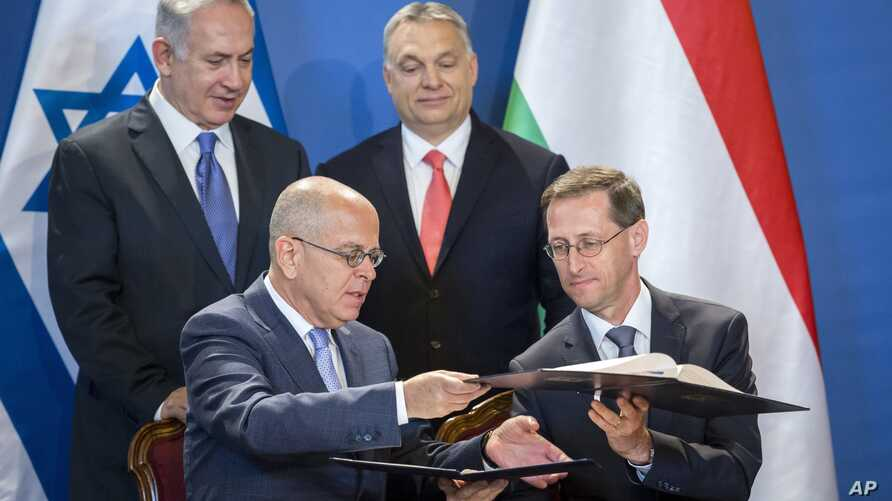 Staying on a four-day official visit in Hungary, Israeli Prime Minister Benjamin Netanyahu, rear left, and his Hungarian counterpart Viktor Orban, rear right, look on as Israeli Ambassador Yosef Amrani, left, and Hungarian Minister of National Econom