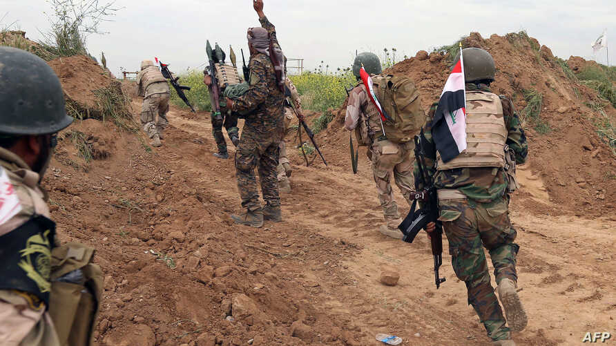 Iraqi Shiite fighters from the Furqat al-Abbas brigades take up their position during an operation to retake the town of al-Bashir, near Kirkuk, from the Islamic State group, April 10, 2016.