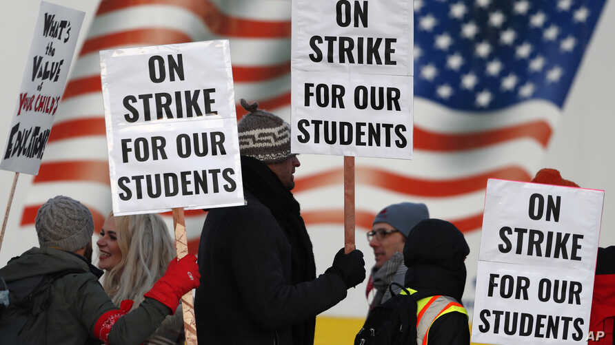 Teachers carry signs as they walk a picket line outside a Denver high school, Feb. 11, 2019.