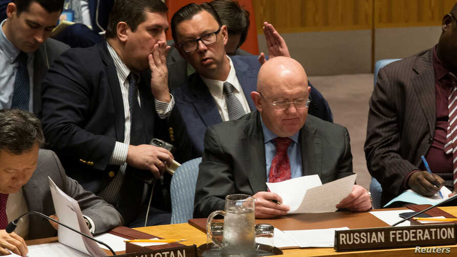Russian diplomats gesture behind Russian Ambassador to the United Nations Vassily Nebenzia during a Security Council meeting at the U.N. headquarters in New York, Sept. 4, 2017.