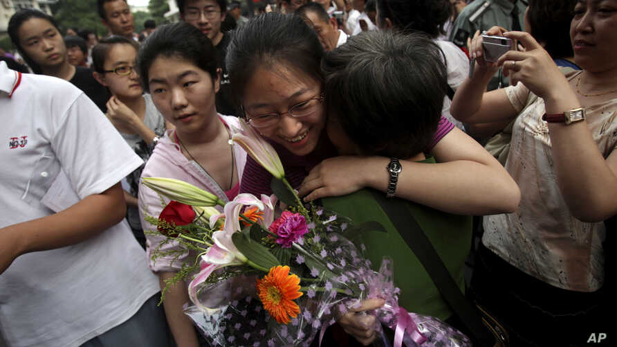 """A Chinese student is greeted by a relative after taking the annual college entrance examinations in Beijing, June 8, 2010. Each year, about over 10 million high school seniors across China take the """"gaokao."""""""