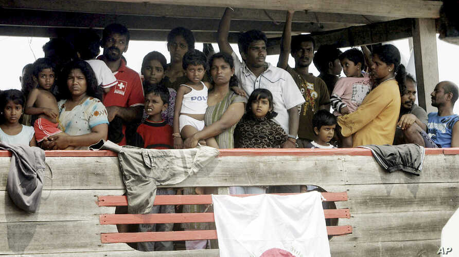 FILE - Sri Lankan migrants bound for Australia remain on board their boat docked at a port in Cilegon, Banten province, Indonesia, after they were intercepted by the Indonesian navy, Oct.14, 2009.